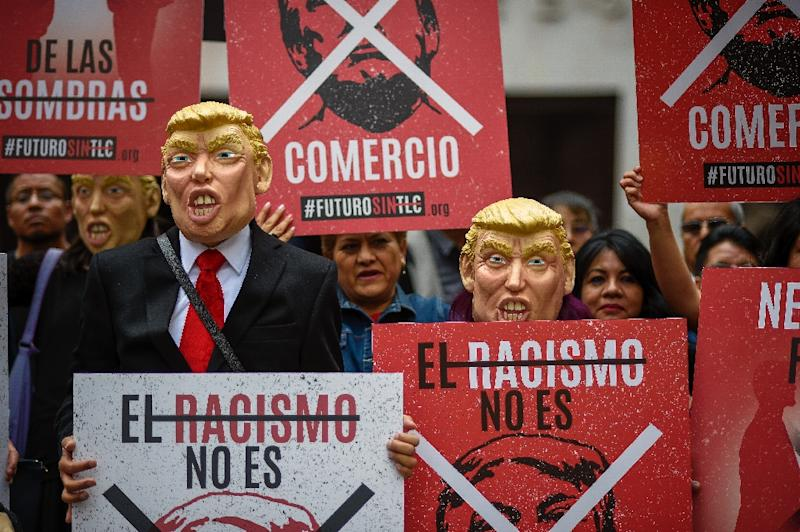 Mexican workers disguised as President Donald Trump protest against his economic policies in late February in Mexico City