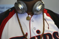 Jalue Dorje wears headphones, a Minnesota Twins jersey, and Tibetan mala beads, which are used to count the repetition of prayers or mantras, as he waits to board a plane bound for New York at the Minneapolis−Saint Paul International Airport on Wednesday, July 21, 2021, in Minneapolis. (AP Photo/Jessie Wardarski)
