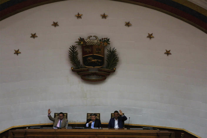 Lawmakers Luis Parra, center, Franklyn Duarte, left, and Jose Noriega, right, vote for the opening of an ordinary session at the National Assembly in Caracas, Venezuela, Tuesday, Jan. 7, 2020. Parra, a former opposition ally, declared himself the National Assembly's leader on Sunday, then today opposition leader Juan Guaidó and opposition lawmakers pushed their way into the legislative building and swore-in Guaido as president of the legislature. (AP Photo/Andrea Hernandez Briceño)