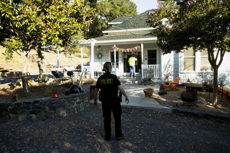 Healdsburg Police Officer Dean confirms residents have evacuated as a wildfire called the Kincade Fire burns nearby on Saturday, Oct. 26, 2019, in Healdsburg, Calif. Authorities issued evacuation orders for the town Saturday morning as the region braces for predicted strong, dry winds Saturday evening. (AP Photo/Noah Berger)