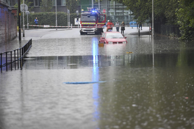 A car is seen stranded in flood water after heavy rain in Manchester, England, Wednesday, July 31, 2019. The UK currently has 10 flood warnings in place from North Yorkshire, Lancashire and the West Midlands. (Jacob King/PA via AP)