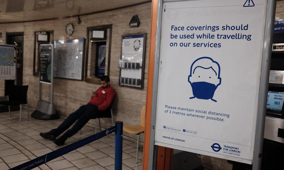 A sign advising the use of face coverings for commuters at Piccadilly Circus underground station in London.