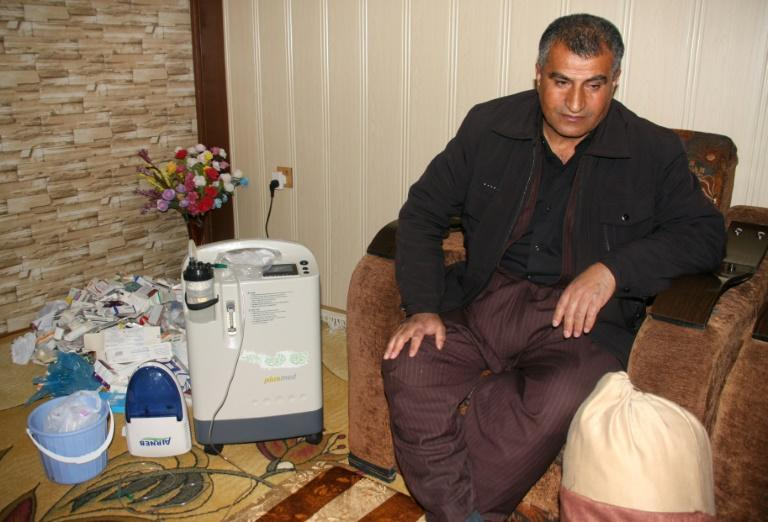 Iraqi Kurd Kamal Jalal, 47, sits next to a machine which helps him breathe, at his home in the Kurdish town of Halabja on March 12, 2018