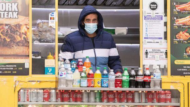 PHOTO: In this Dec. 31, 2020, file photo, a worker wears a face mask inside a food truck in Columbus Circle in New York. (Noam Galai/Getty Images, FILE)