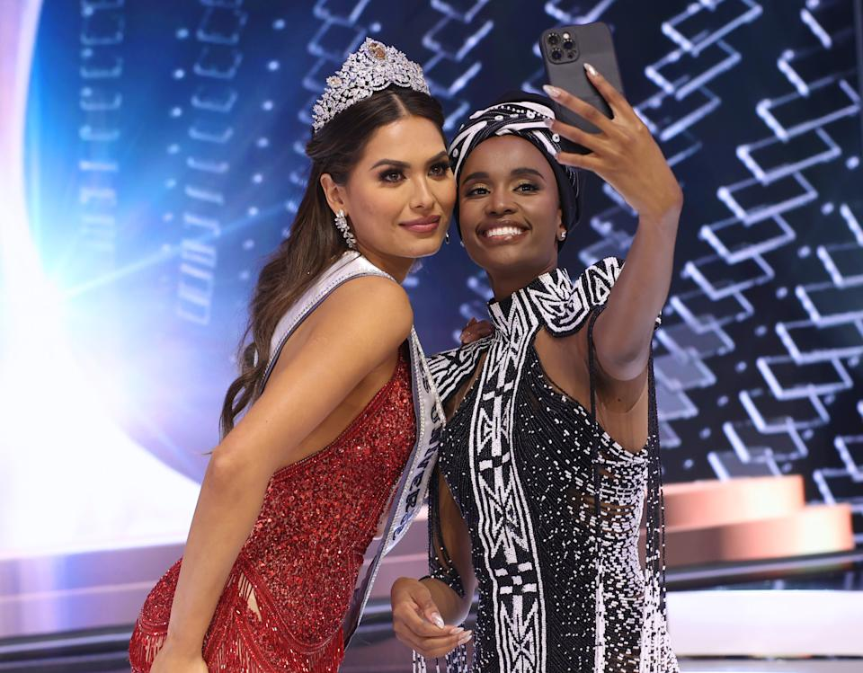 HOLLYWOOD, FLORIDA - MAY 16: Miss Universe 2020 Andrea Meza and Miss Universe 2019 Zozibini Tunzi take a selfie onstage at the 69th Miss Universe competition at Seminole Hard Rock Hotel & Casino on May 16, 2021 in Hollywood, Florida. (Photo by Rodrigo Varela/Getty Images)