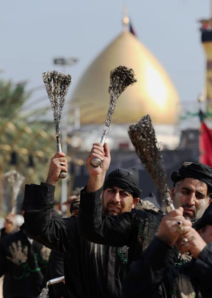"""Shiite faithful worshippers beat themselves with chains as a sign of grief for Imam Hussein during """"Muharram,"""" an important period of mourning for Shiites, standing between the holy shrines of Imam Hussein and Imam Abbas, seen in the background, in Karbala, 50 miles (80 kilometers) south of Baghdad, Iraq, Wednesday, Nov. 13, 2013. The remembrance of Muharram marks the anniversary of the Battle of Karbala when Imam Hussein, a grandson of Prophet Muhammad, was killed. (AP Photo/Hadi Mizban)"""