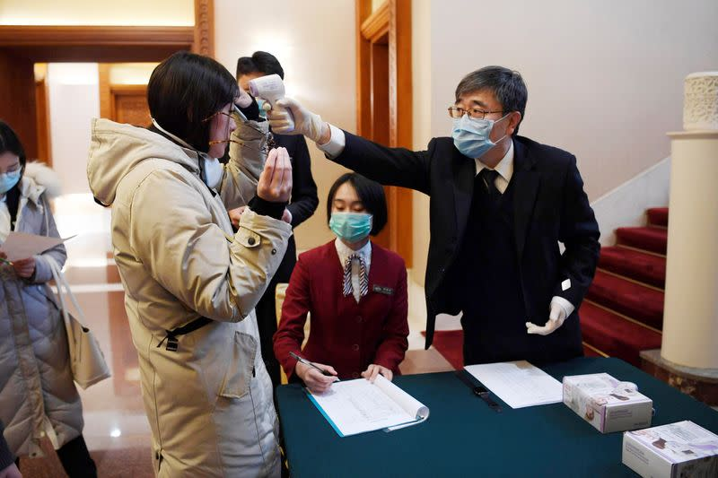 A man uses a thermometer to check the temperature of a journalist covering a meeting between Tedros Adhanom, director general of the World Health Organization, and Chinese Foreign Minister Wang Yi at the Diaoyutai State Guesthouse in Beijing