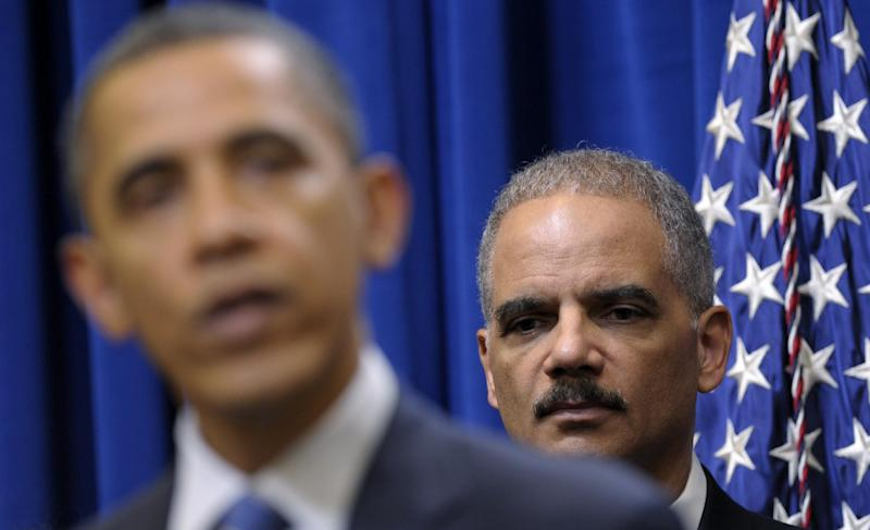 FILE - In this Feb. 9, 2012 file photo, Attorney General Eric holder listens at right as President Barack Obama speaks about a mortgage settlement in the Eisenhower Executive Office building on the White House complex in Washington. Wednesday, President Obama refused to turn over some Justice Department documents about a botched anti-smuggling operation that allowed hundreds of guns sold in Arizona to end up in Mexico. Because of the standoff, the House Government Oversight and Reform Committee then voted to hold Attorney General Eric Holder in contempt of Congress. (AP Photo/Susan Walsh)
