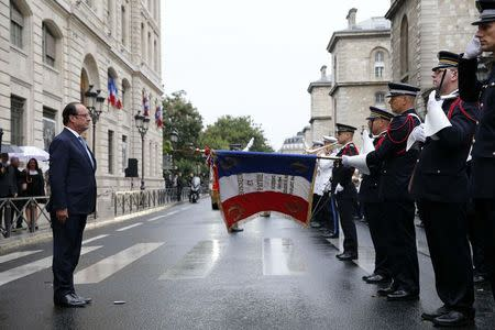 French President Francois Hollande (L) listens to the national anthem during a ceremony to mark the 70th anniversary of the Liberation of Paris from Nazi occupation, at the Police headquarters in Paris, August 25, 2014. REUTERS/Yoan Valat/Pool