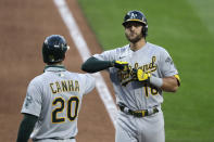 Oakland Athletics' Chad Pinder, right, is greeted by Mark Canha at home after hitting a two-run home run against the Seattle Mariners in the seventh inning of a baseball game Saturday, Aug. 1, 2020, in Seattle. (AP Photo/Elaine Thompson)