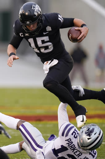 Iowa State quarterback Brock Purdy (15) leaps over Kansas State defensive back AJ Parker (12) during the first half of an NCAA college football game, Saturday, Nov. 21, 2020, in Ames, Iowa. (AP Photo/Charlie Neibergall)