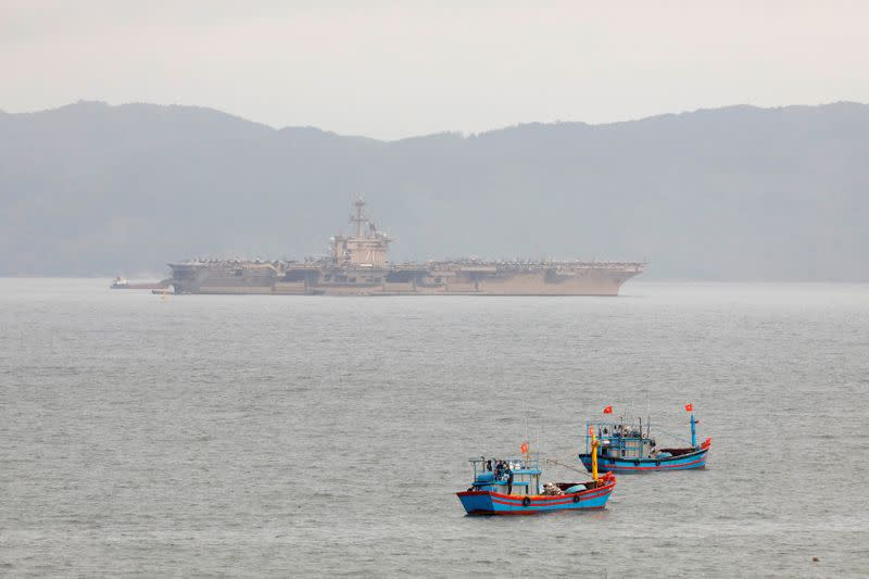 FILE PHOTO: The USS Theodore Roosevelt (CVN-71) is seen near Vietnamese fishing boats at a port in Da Nang city