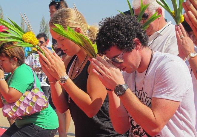 This handout picture taken by BEC Tero on December 30, 2011 shows women's world tennis number one Caroline Wozniacki of Denmark (L) and men's world number three golfer Rory McIlroy (R) of Northern Ireland praying at the buddhist temple in Hua Hin resort.  Wozniacki has arrived in Thailand for a charity tennis match against Victoria Azarenka to raise money for the country's recent flood crisis, a spokeswoman said December 30. (Photo by Ho/bec Tero/AFP/Getty Images)