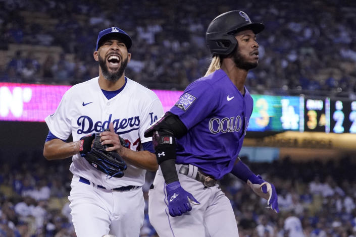 Los Angeles Dodgers starting pitcher David Price, left, reacts after his errant throw to first allowed Colorado Rockies' Raimel Tapia, right, to advance to second during the third inning of a baseball game Friday, July 23, 2021, in Los Angeles. (AP Photo/Mark J. Terrill)