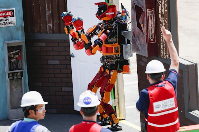The Team Nedo-JSK robot is awarded a point after opening and walking through a door during the finals of the Defense Advanced Research Projects Agency (DARPA) Robotic Challenge in Pomona, California June 6, 2015. DARPA challenges are an example of a public-private cyber initiative.