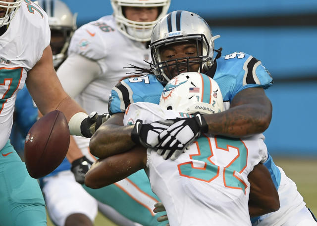 Miami Dolphins' Kenyan Drake (32) fumbles the ball as he is hit by Carolina Panthers' Dontari Poe (95) in the first half of a preseason NFL football game in Charlotte, N.C., Friday, Aug. 17, 2018. The Dolphins recovered the ball. (AP Photo/Mike McCarn)