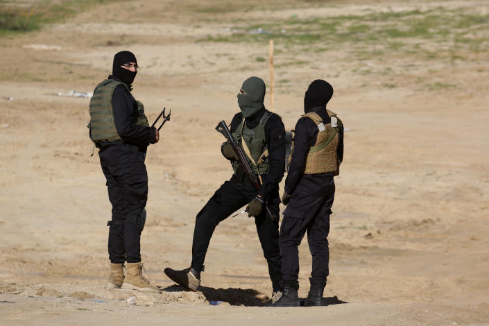 Palestinian militants stand guard during a military drill organized by military factions outside Gaza City, Tuesday, Dec. 29, 2020. Palestinian militants in the Gaza Strip fired a salvo of rockets into the Mediterranean Sea on Tuesday as part of a self-styled military drill aimed at preparing for a possible war with Israel. (AP Photo/Adel Hana)