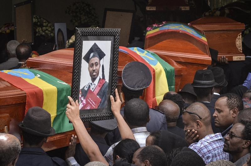 Mourners carry portraits of victims of the crashed accident of Ethiopian Airlines during a mass funeral at Holy Trinity Cathedral in Addis Ababa, Ethiopia in March (AFP Photo/Samuel HABTAB)