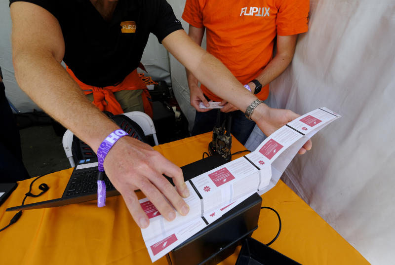 ** HOLD FOR STORY ** In this photo taken Friday, June 21, 2019, FlipTix workers load a ticket printer in their tent at the entrance to the Clusterfest comedy event in San Francisco. The company's application lets people who leave a venue early sell their ticket and lets someone who wants the remainder of the ticket buy it. (AP Photo/Eric Risberg)