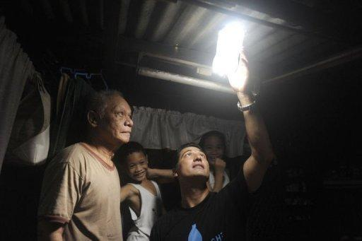 Illac Diaz (R) and Siplicio Mondas inspect a solar light bottle installed by Philippine soldiers in a shanty town in Manila. With the help of some plastic bottles plus a social media campaign, Diaz is aiming to help a million poor people in a year