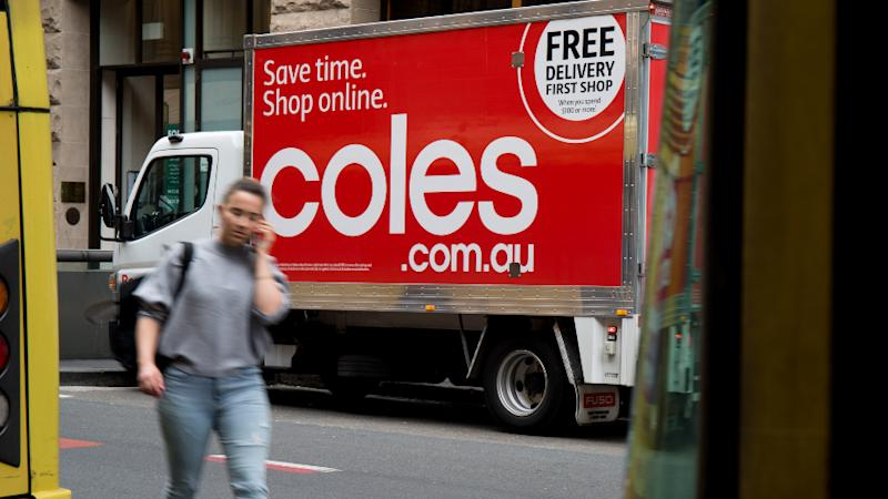 A woman walking by a Coles van on the street.