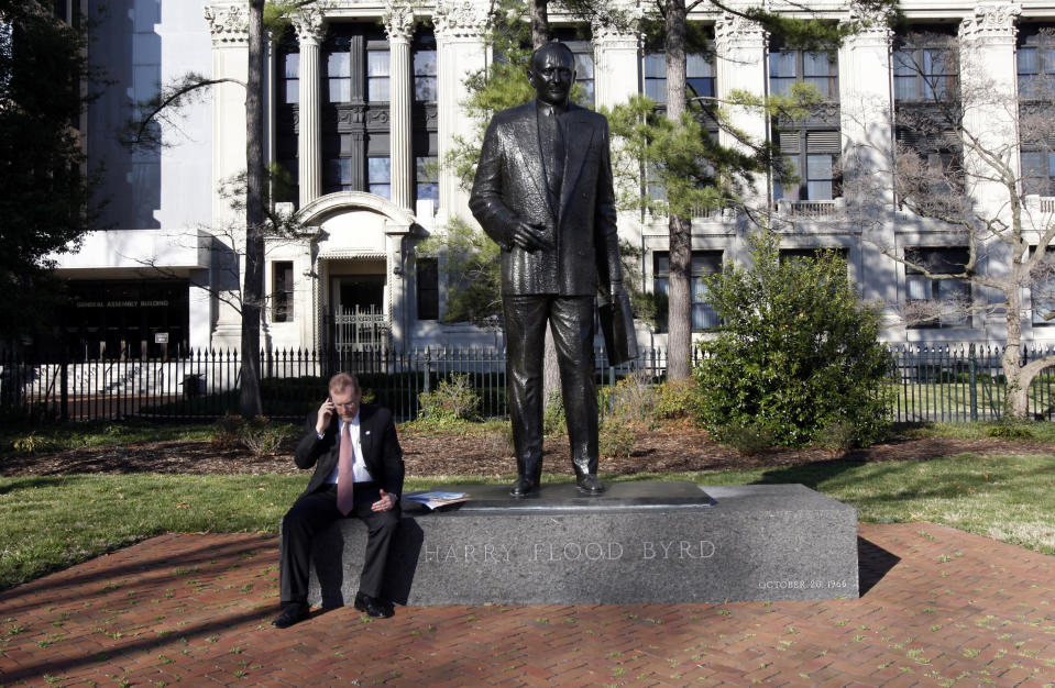 FILE - In this Saturday, March 13, 2010, file photo, House Majority Leader H. Morgan Griffith, R-Salem, talks on a phone as he sits at the feet of the statue of former governor and U.S. Sen. Harry F. Byrd at Capitol Square in Richmond, Va. Work is expected to begin Wednesday, July 7, 2021, to remove a statue of Harry F. Byrd Sr., a staunch segregationist, from the state's Capitol Square. (Bob Brown/Richmond Times-Dispatch via AP, File)