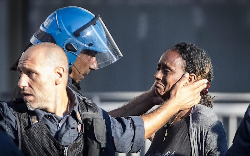 A police officer comforts a refugee during protests against a mass eviction in Rome - ANSA