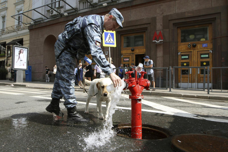 A policeman gets water for his dog outside a subway station in downtown Moscow on Wednesday, June 5, 2013. A rush-hour fire in Moscow's subway injured dozens of people, forced the evacuation of thousands of commuters and closed parts of the network on Wednesday, authorities said. As firefighters were putting out the fire, authorities closed one of the subway lines that cuts through central Moscow. Eyewitnesses say central Moscow streets were thronged with crowds who ended up walking to work. (AP Photo/Denis Tyrin)