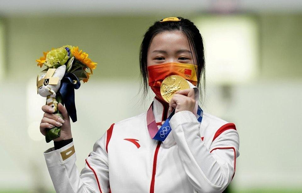 China's Qian Yang celebrates with her gold medal after winning the 10m air rifle women's final at the Asaka Shooting Range on the first day of the Tokyo 2020 Olympic Games. Photo: Getty