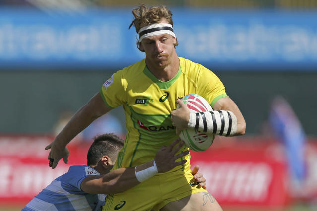 "FILE - In this Dec. 1, 2018, file photo, Australia's Ben O'Donnell is tackled by Argentina's player in a quarterfinal match of the Emirates Airline Rugby Sevens in Dubai, the United Arab Emirates. ODonnell thought his Olympic dream was over just two months ago when he injured his knee and was given no chance of recovering by July. So while the coronavirus pandemic-enforced postponement of the Tokyo Games to 2021 has been met with disappointment from the worlds leading athletes, the rugby sevens player is struggling to contain his smile. He says the Olympic postponement has ""given a little opening in the door for me."" (AP Photo/Kamran Jebreili, File)"