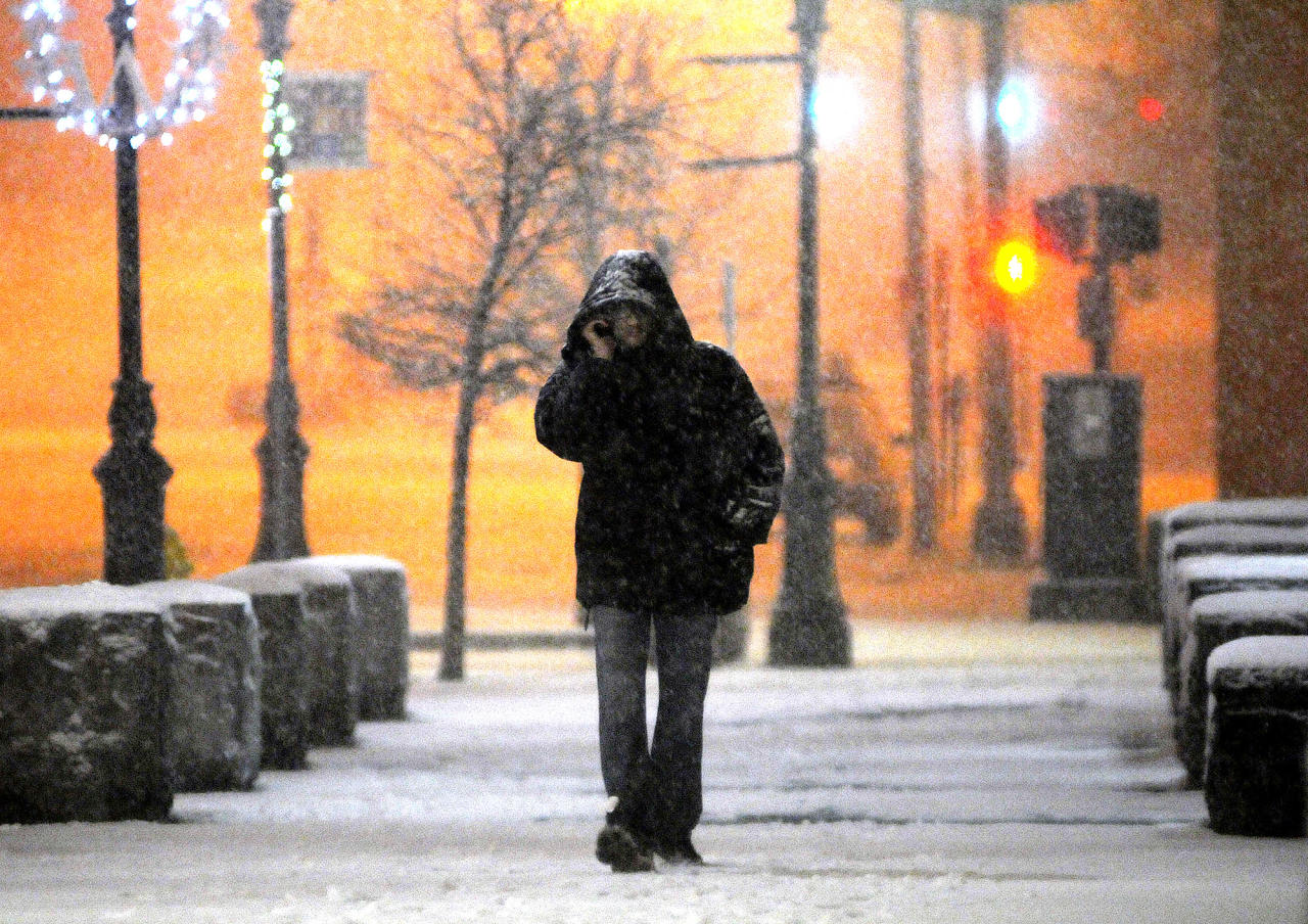 In this Wednesday, Dec. 26, 2012 photo, a man talks on his cellphone, as he walks along Main Street during a snowstorm late Wednesday night. The winter storm brought snow to inland parts of the Northeast and driving rain and wind to areas along the coast Thursday, a day after it swept through the nation's middle, dumping a record snowfall in Arkansas and wrecking post-holiday plans for thousands of travelers. (AP Photo/The Telegram & Gazette, Steve Lanava)