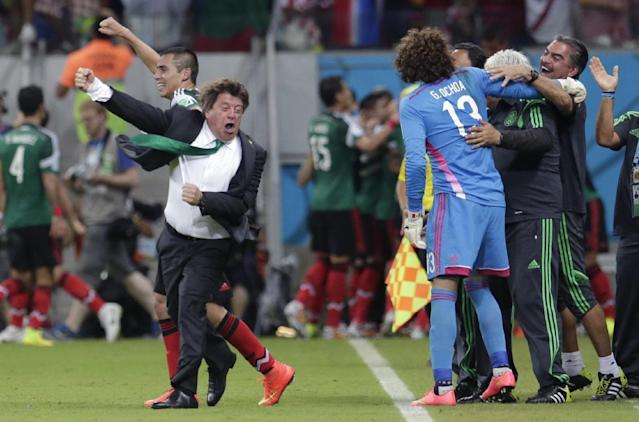 In this June 23, 2014 photo, Mexico's head coach Miguel Herrera celebrates after Mexico's Andres Guardado scored his side's second goal during the group A World Cup soccer match between Croatia and Mexico at the Arena Pernambuco in Recife, Brazil. Mexico's national soccer coach just can't keep his joy bottled up, and his enthusiasm has made him one of the most entertaining and popular figures of the World Cup and an Internet sensation worldwide. (AP Photo/Petr David Josek)