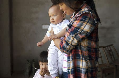 Liu Guimei holds her grandson, Xu Ning, next to granddaughter Xu Yilin, whose blood, according to her family, has been shown to have almost three times the national limit for lead exposure in children, in Dapu town, Hunan province, June 25, 2014. REUTERS/Alexandra Harney