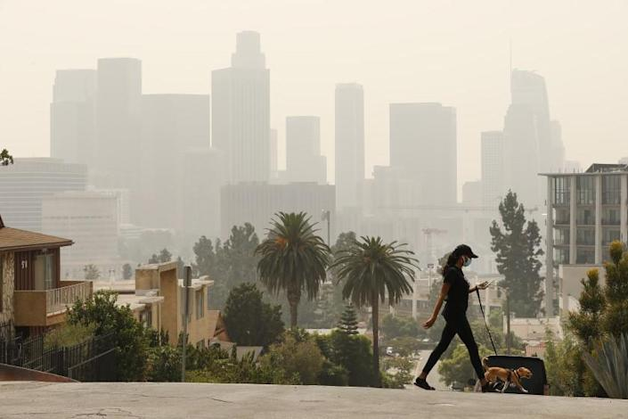 """LOS ANGELES, CA - SEPTEMBER 14: Breya Hodge walks her dog """"Sophie"""" as smoke and ash from the Bobcat fire burning in the Angeles National Forest have blanketed the region for a week, contributing to poor air quality which nearly obscures the tall buildings of downtown Los Angeles September 14, 2020. Current air quality readings are considered unhealthy for sensitive groups according to the Environmental Protection Agency. The bobcat fire is one of more than 25 fires burning in California creating a plume that spanned more than 1,000 miles. Downtown on Monday, Sept. 14, 2020 in Los Angeles, CA. (Al Seib / Los Angeles Times"""