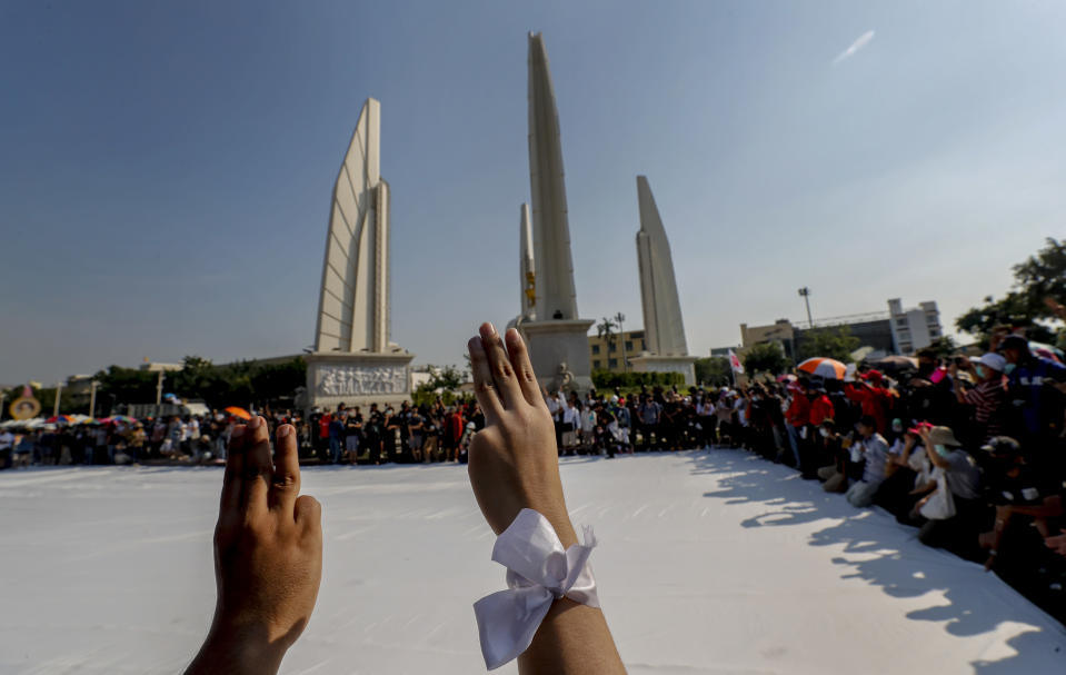 Students led pro-democracy protesters flash three-finger salute as they gather for a rally at the Democracy Monument in Bangkok, Thailand, Saturday, Nov. 14, 2020. (AP Photo/Sakchai Lalit)
