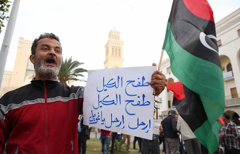 "A supporter of Libya's UN-backed prime minister-designate Fayez al-Sarraj holds a poster reading: ""Fed up, fed up, leave, leave Ghweil"" in reference to the unrecognised government's prime minister Khalifa Ghweil, in Tripoli on March 31, 2016 (AFP Photo/Taha Jawashi)"