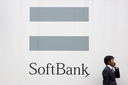 FILE PHOTO: A man talks on the phone as he stand in front of an advertising poster of the SoftBank telecommunications company in Tokyo