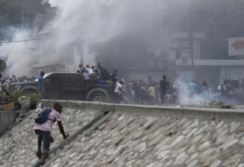 Demonstrators are sprayed by a police water cannon during a protest calling for the resignation of President Jovenel Moise, in Port-au-Prince, Haiti, Friday, Oct. 4, 2019. After a two-day respite from the recent protests that have wracked Haiti's capital, opposition leaders urged citizens angry over corruption, gas shortages, and inflation to join them for a massive protest march to the local headquarters of the United Nations. (AP Photo/Rebecca Blackwell)