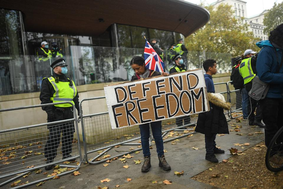 LONDON, ENGLAND - OCTOBER 24: A protester holds a sign reading 'Defend Freedom' during a Unite for Freedom march outside New Scotland Yard on October 24, 2020 in London, England. Hundreds of anti-mask and anti-lockdown protesters marched through central London, England demonstrating against latest Coronavirus lockdown measures. (Photo by Peter Summers/Getty Images)