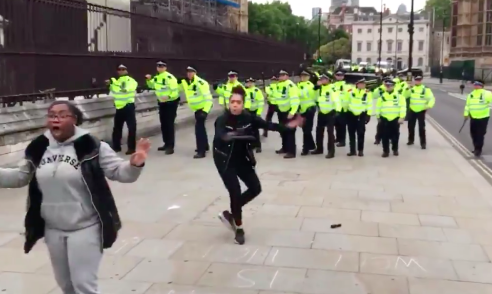 Two women stood between retreating police and protesters in central London on Sunday (Matthew Thompson/Twitter)