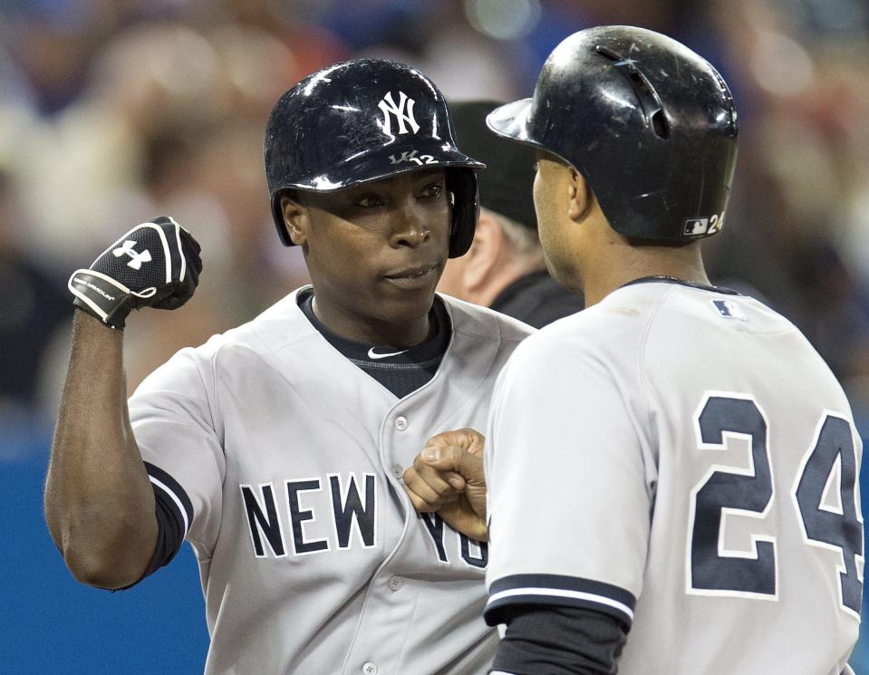 New York Yankees' Alfonso Soriano, left, is congratulated by Robinson Cano after hitting a three-run home during against the Toronto Blue Jays during the first inning of a baseball in Toronto on Tuesday, Aug. 27, 2013. (AP Photo/The Canadian Press, Frank Gunn)