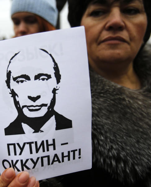"A woman holds a banner that reads: ""Putin is Occupier"" during a rally against the breakup of the country in Simferopol, Crimea, Ukraine, Tuesday, March 11, 2014. The Crimean parliament voted Tuesday that the Black Sea peninsula will declare itself an independent state if its residents agree to split off from Ukraine and join Russia in a referendum. Crimea's regional legislature on Tuesday adopted a ""declaration of independence of the Autonomous Republic of Crimea."" The document specified that Crimea will become an independent state if its residents vote on Sunday in favor of joining Russia in the referendum. (AP Photo/Darko Vojinovic)"
