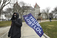 """Christina Janowitz of Guilderland, N.Y., from the group """"All Of Us' holds a flag while counter-protesting a Trump rally ahead of the inauguration of President-elect Joe Biden and Vice President-elect Kamala Harris at the New York State Capitol Sunday, Jan. 17, 2021, in Albany, N.Y. (AP Photo/Hans Pennink)"""