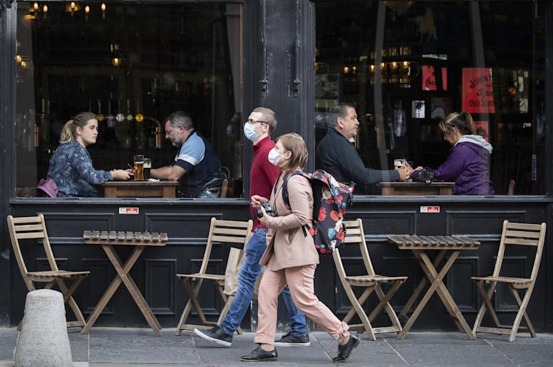 People wearing protective face masks walk past a bar in Edinburgh city centre, after First Minister Nicola Sturgeon announced a range of new measures to combat the rise in coronavirus cases in Scotland. (Photo by Jane Barlow/PA Images via Getty Images)
