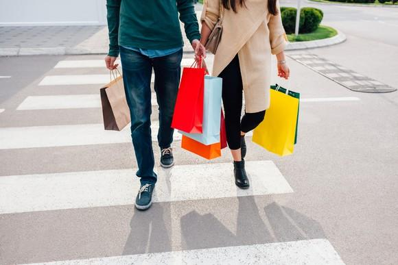 Two people walking on a street, holding shopping bags.