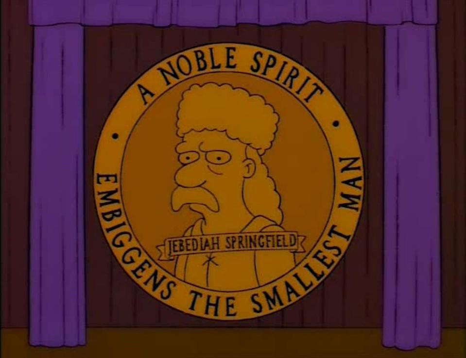 A giant emblem of Jebediah Springfield against a purple curtain from The Simpsons