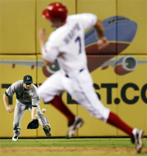 Texas Rangers' David Murphy, right, advances to third as Oakland Athletics left fielder Brandon Moss fields a single by Rangers' Mitch Moreland during the second inning of a baseball game, Monday, Sept. 24, 2012, in Arlington, Texas. Rangers' Michael Young scored on the single. (AP Photo/Tony Gutierrez)