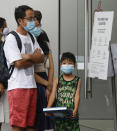Shoppers wear masks as they wait to enter a store at a shopping precinct in Sydney, Australia, Sunday, Jan. 3, 2021. Masks have been made mandatory in shopping centers, on public transport, in entertainment venues such as a cinema, and fines will come into effect on Monday as the state government responds to the COVID-19 outbreak on Sydney's northern beaches, which is suspected to have also caused new cases in neighboring Victoria state. (AP Photo/Mark Baker)