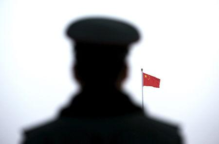 A paramilitary policeman watches a flag-raising ceremony at Tiananmen Square ahead of the opening session of the National People's Congress in Beijing, China