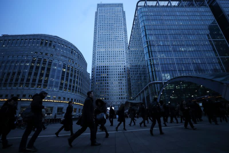 FILE PHOTO: Workers walk to work during the morning rush hour in the financial district of Canary Wharf in London